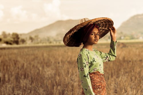 Photo of Woman Standing While Wearing Straw Hat