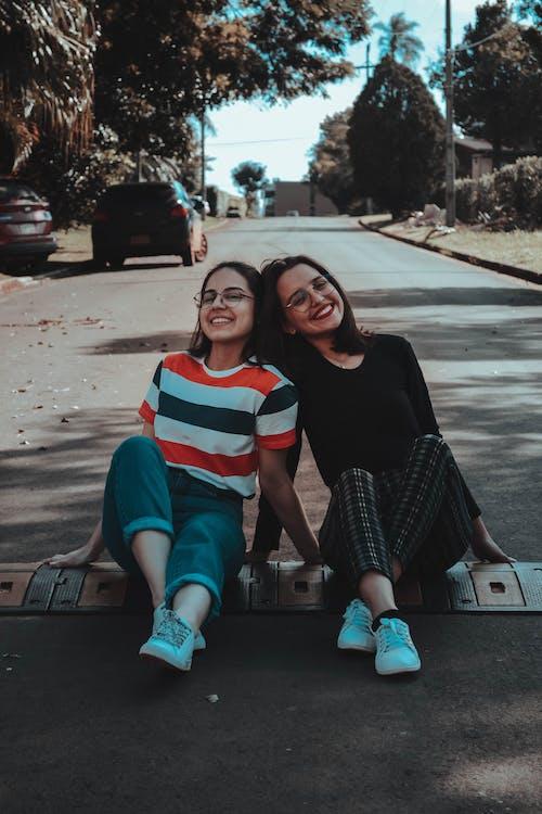 道路に座っている2人の女性の写真