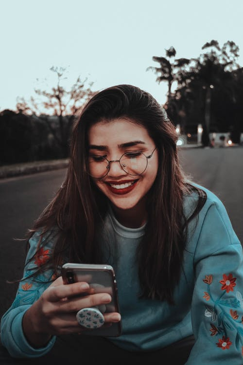 Photo of Woman Smiling While Looking at Smartphone