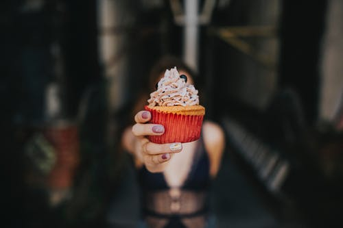 Selective Focus Photography Of Woman Holding Cupcake