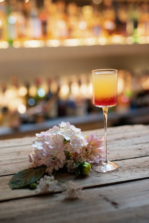 Glass of cocktail with flowers on table