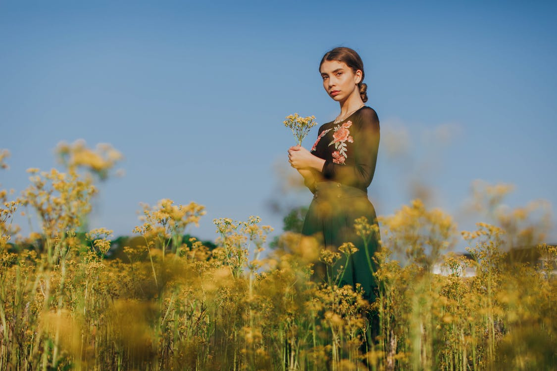 Selective Focus Photography of a Woman Standing on a Flower Field