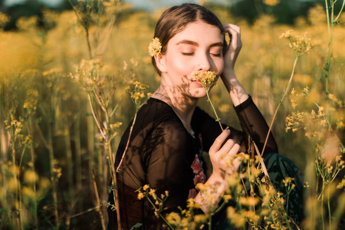 Photo of Woman Smelling Yellow Flower