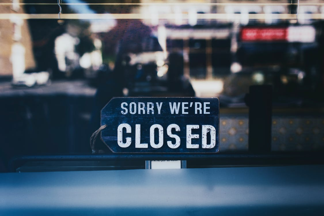 Close-Up Photo of Sorry We're Closed Sign on Glass Window
