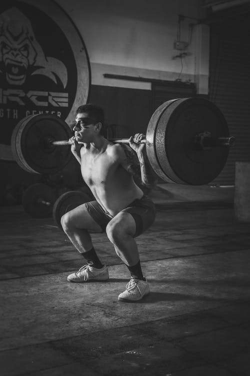Monochrome Photo of Man Holding Barbell
