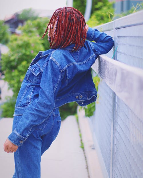 Back View Photo of Woman in Denim Outfit Leaning Against Metal Fence