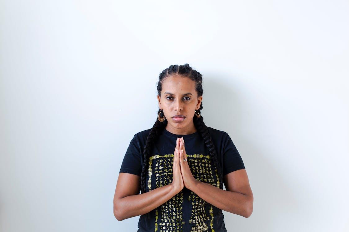 Woman Wearing Black and Yellow Crew-neck T-shirt Praying