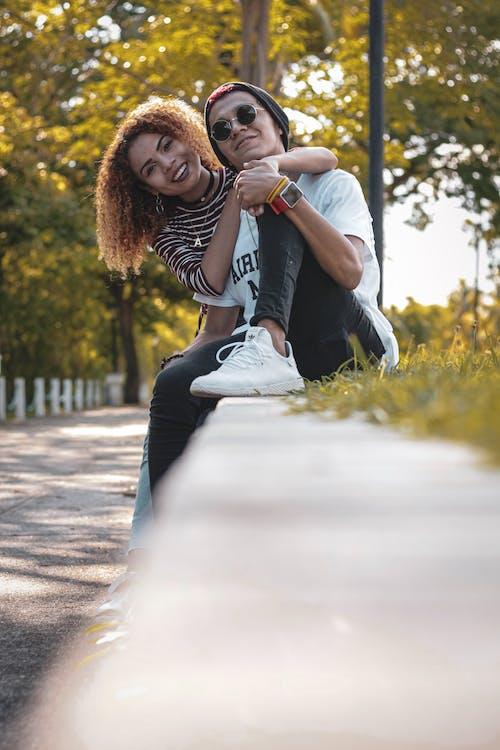 Foto profissional grátis de abraçando, alegre, amor, ao ar livre