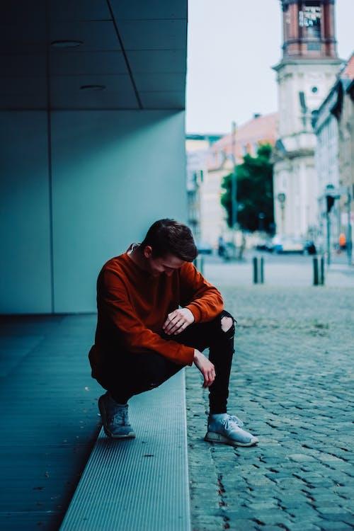 Photo of Man Wearing Orange Sweater