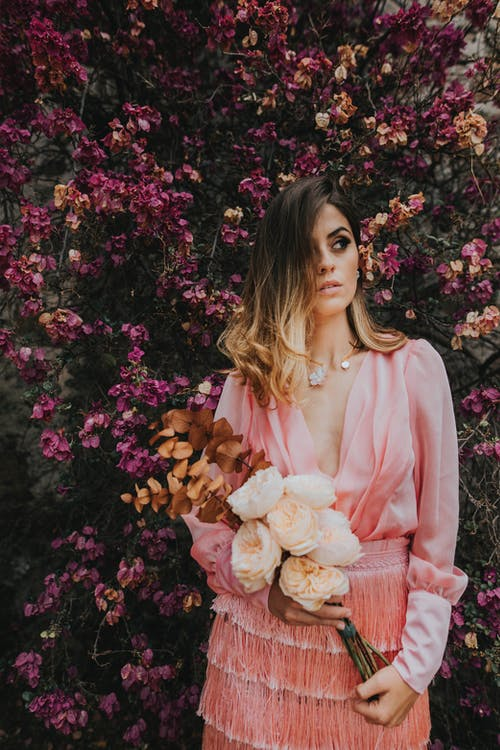 Photo of Woman Standing in Front of Flowers