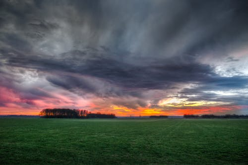 Storm Clouds over Field During Sunset