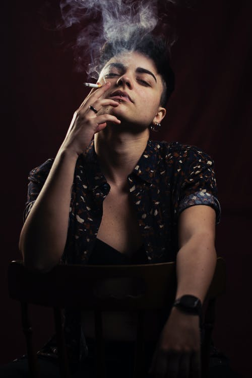 Photo of Person Smoking While Sitting on Chair