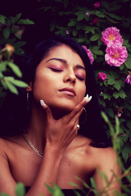 Photo of Woman With Eyes Closed Holding Her Chin Standing Beside  Flowers