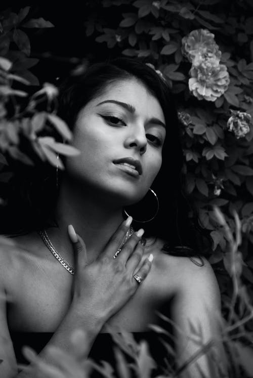 Grayscale Portrait Photo of Woman Posing by Flowers