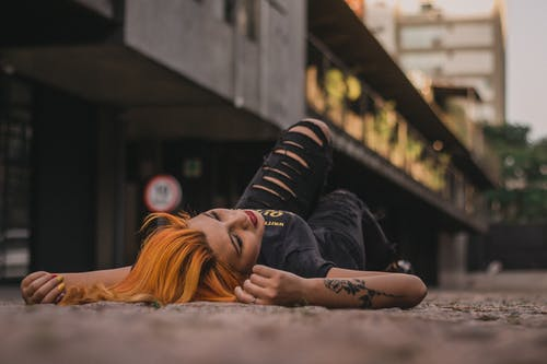 Photo of a Woman Lying on Her Back  Near a Building