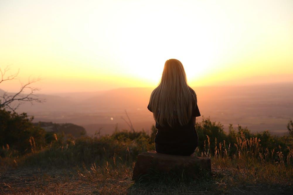 Femme regardant le coucher du soleil | Photo : Pexels