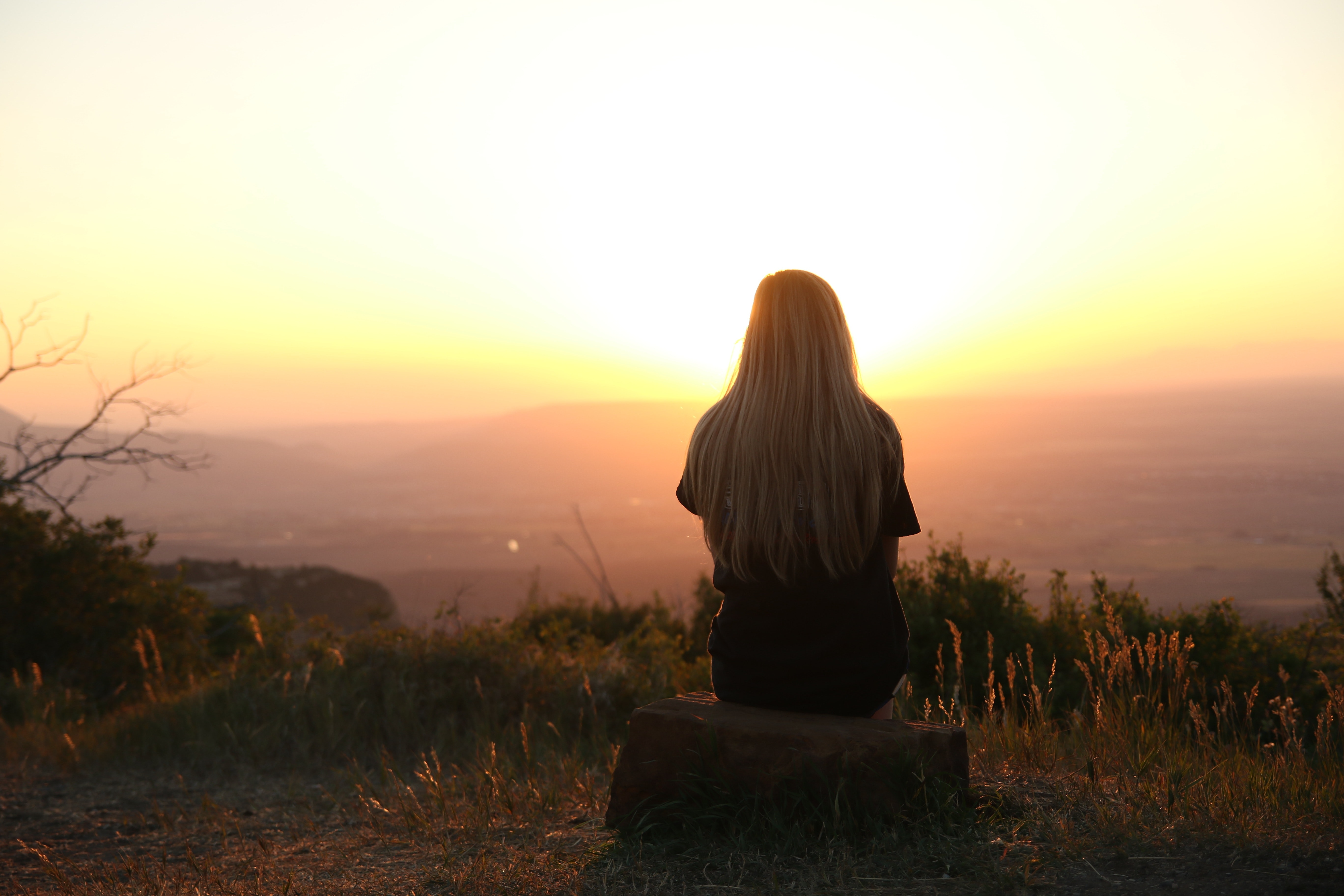 Woman looking at the sunset. | Photo: Pexels
