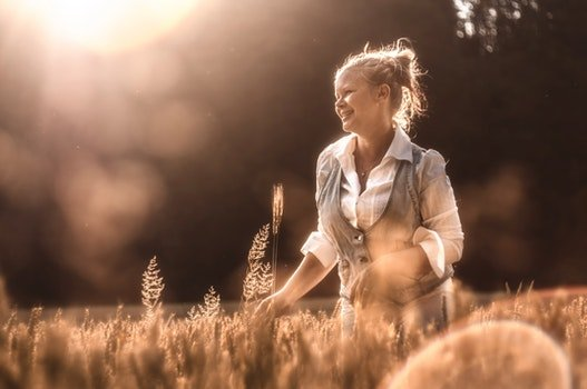 Mid Adult Woman in Wheat at Sunset