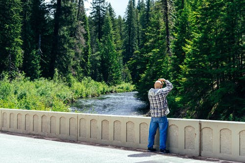 Photo of Man Standing While Taking Picture of Trees and River