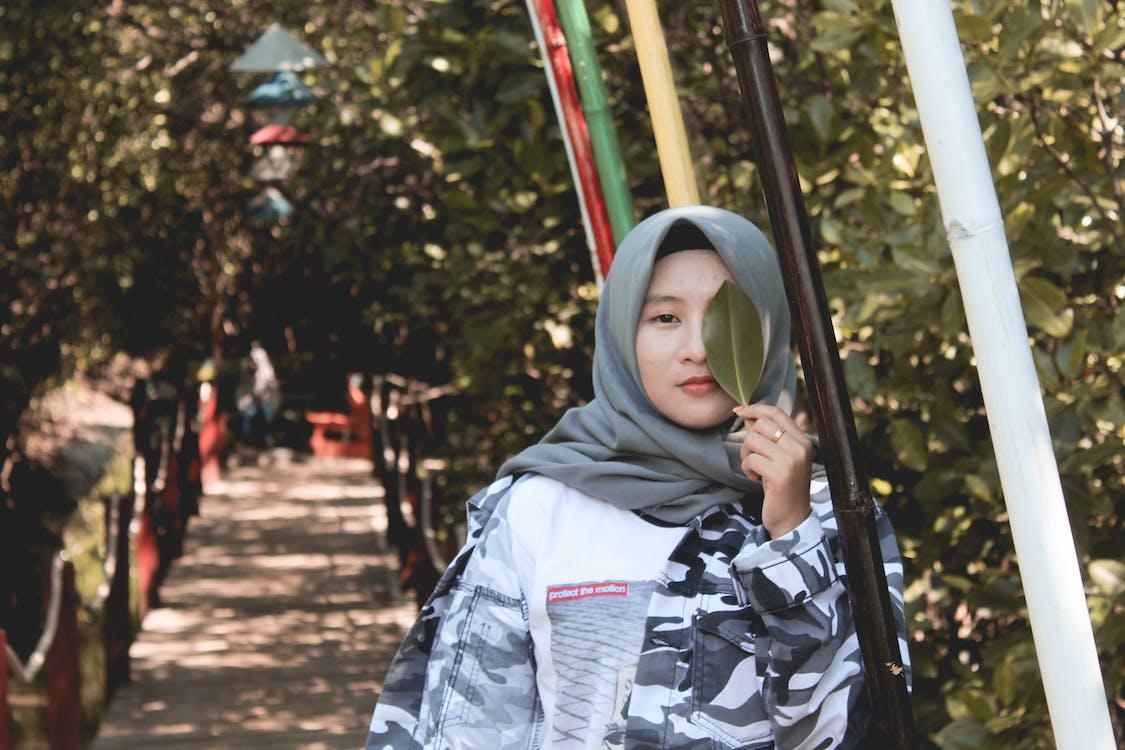 Foto Perempuan Menutup Mata Kiri Dengan Daun Hijau