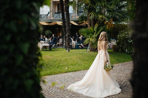 Woman Wearing Wedding Dress and Holding a Bouquet of Flowers Standing on Brick Pathway