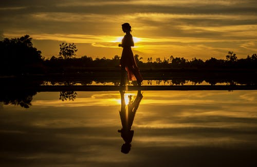 Silhouette of Man Standing on Lake at Sunset