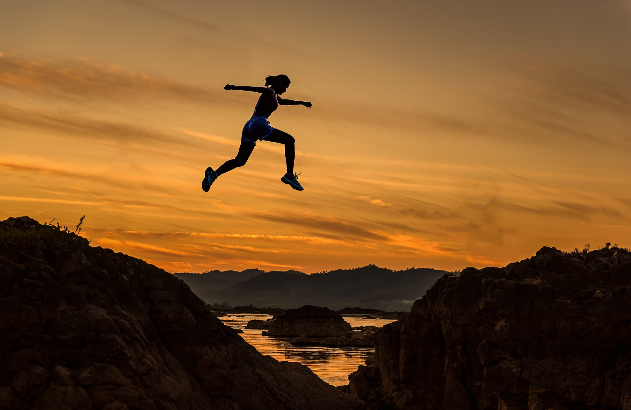 Man Jumping on Landscape at Sunset