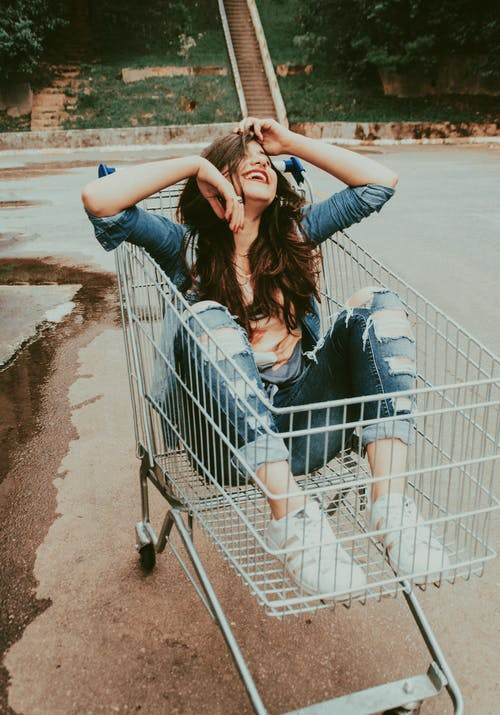 Photo of Woman Sitting in Shopping Cart