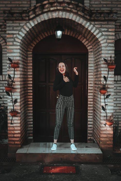 Photo of Woman Standing in Front of Wooden Door