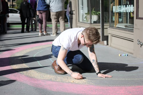 Photo of a Man in White T-Shirt Coloring on Gray Pavement Next to a Building