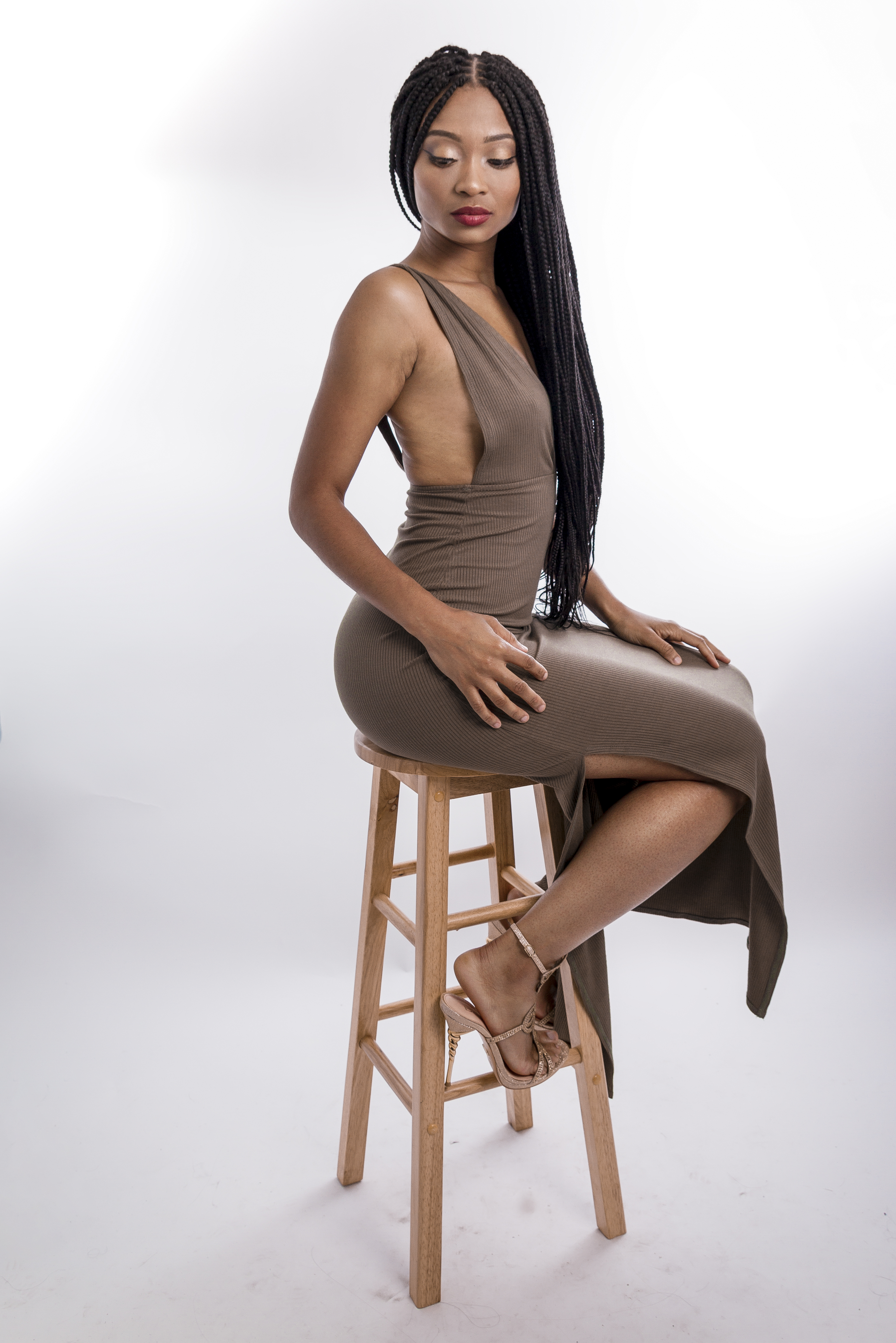Photo of Woman Wearing Brown Dress While Sitting on Stool