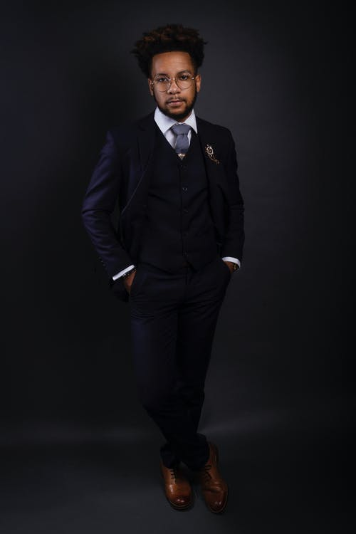 Photo of a man wearing a black three piece suit