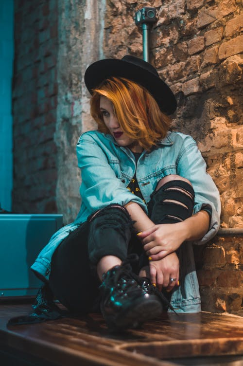 Photo of Woman Wearing Blue Denim Jacket Sitting Beside Wall