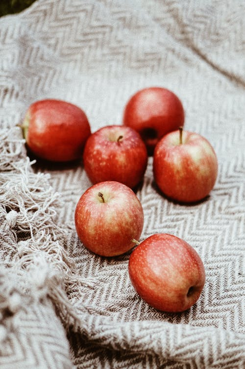 Six Red Apples on Grey Blanket