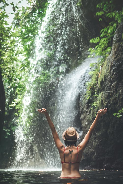 Photo of a woman wearing a red bikini standing in the water near a waterfall