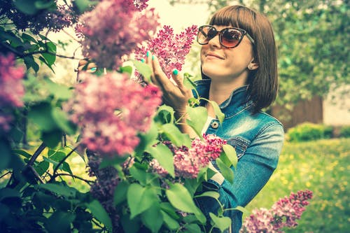 Photo of a woman wearing sunglasses holding lilac flowers