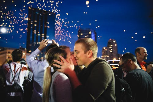 Photo of Couple Kissing Near Crowd