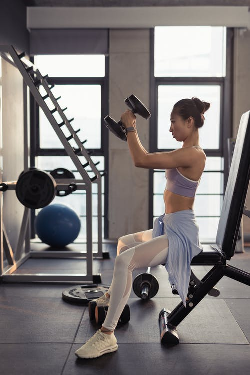 Photo of Woman Sitting and Raising Dumbbells