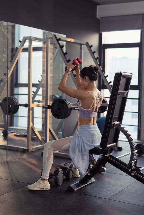 Photo of Woman Raising Dumbbells in Gym