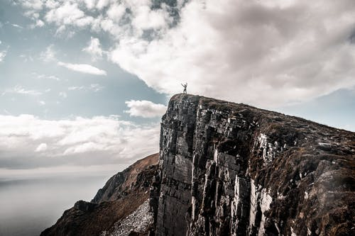 Scenic Photo of Man Standing on Cliff Edge