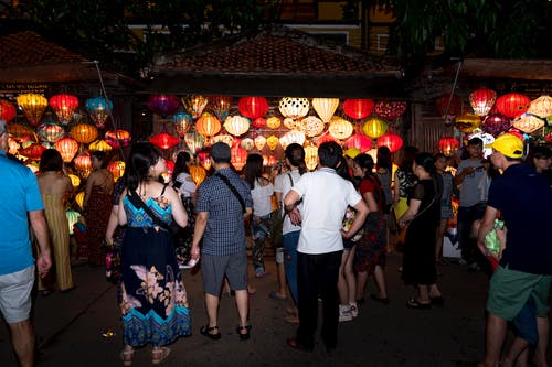 Photo of People Standing Near Lighted Lanterns