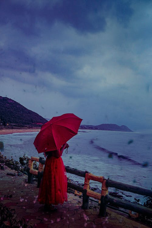 Photo of Person Wearing Red Dress While Holding Red Umbrella