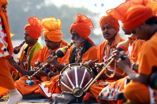 Men in Orange Costumes Playing Instruments