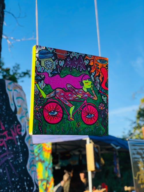 Shallow Focus Photo of Woman Riding Bike Painting