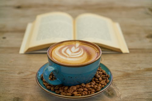Blue Ceramic Teacup With Saucer Beside Book