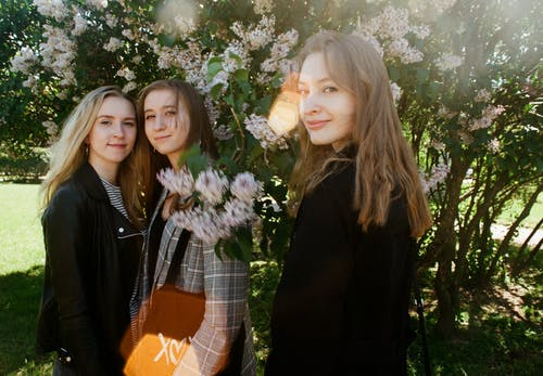 Photo of Three Women Standing Near White Petaled Flowers