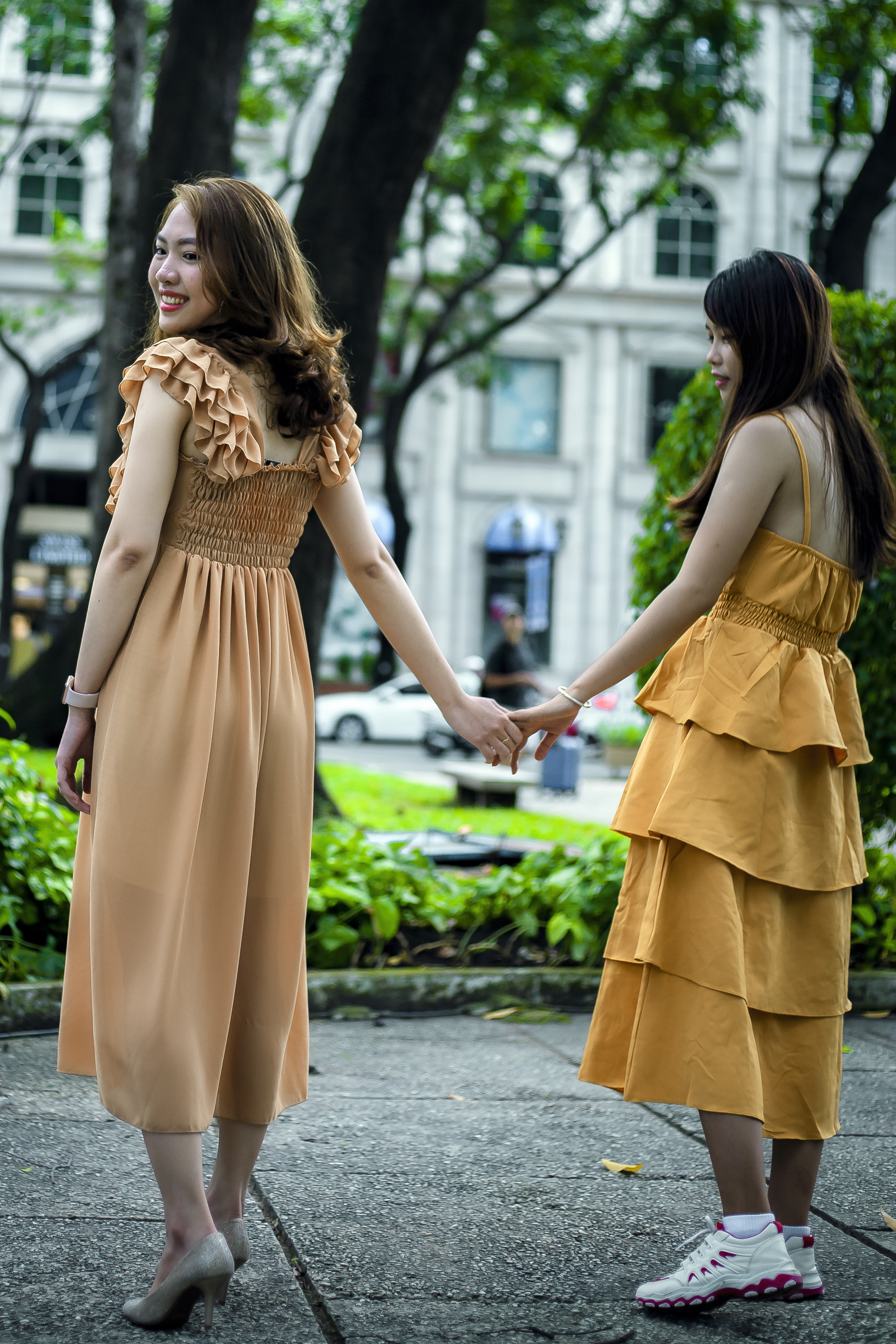 Photo of Women Wearing Dress While Holding Hands