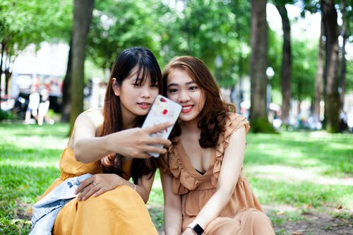 Photo of Two Woman Taking Selfie While Sitting on Grass