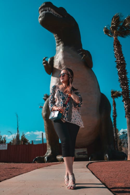 Photo of a woman wearing a printed top and sunglasses standing  near dinosaur figurine