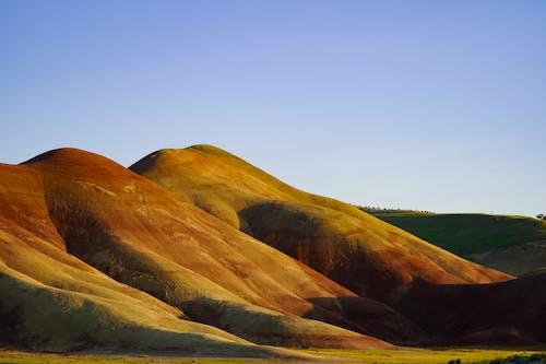 Landscape Photo of Hills Under Blue Sky